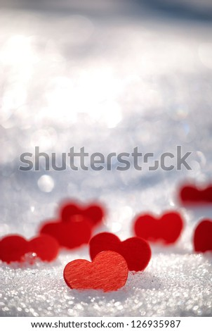Red hearts on glittering snow with shallow depth of field - stock photo