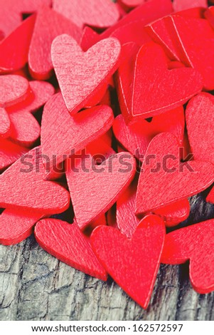 red hearts on rustic wooden surface - stock photo