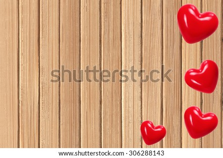 Red hearts over wood texture close-up - stock photo