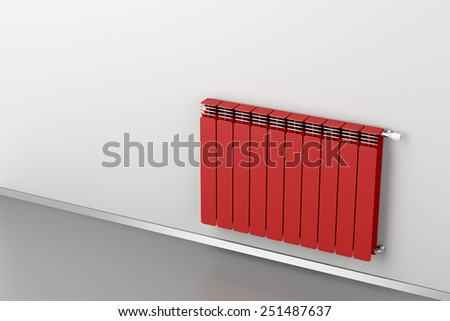 Red heating radiator attached on grey wall  - stock photo