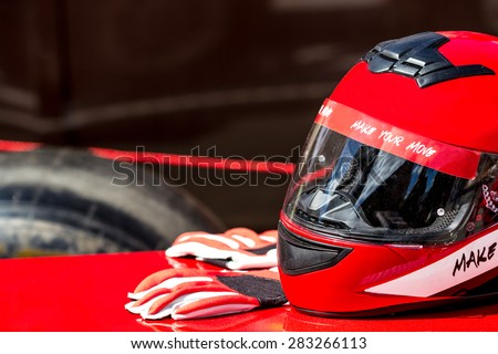 Red helmet with gloves for riding on a racing car - stock photo