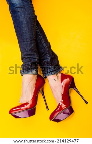 red high heels on a yellow background - stock photo