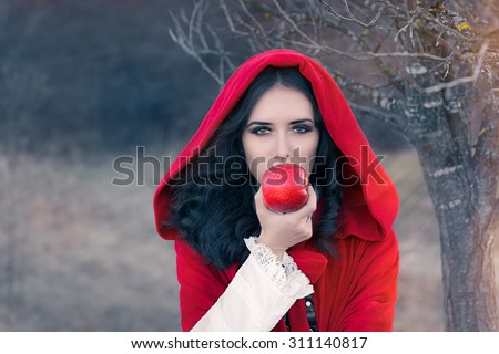 Red Hooded Woman Holding Apple Fairytale Portrait - Fairytale image of a beautiful  girl wearing a red hood near the forest  - stock photo