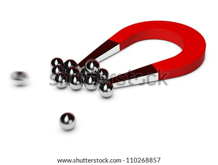 red horseshoe magnet attracting some chrome balls, white background - stock photo