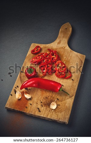 Red Hot Chili Pepper, Spice and Organic Garlic on Wooden Kitchen Plate as Hot Food Ingredients for Spicy Piquant Cuisine. - stock photo