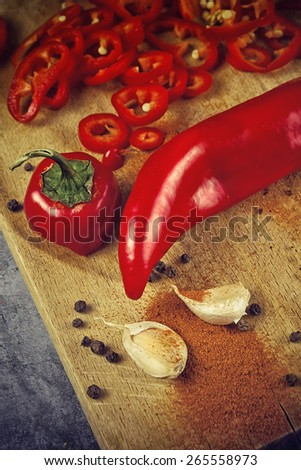Red Hot Chili Pepper, Spice and Organic Garlic on Wooden Kitchen Plate as Hot Food Ingredients for Spicy Piquant Cuisine. Selective focus with shallow depth of field. - stock photo