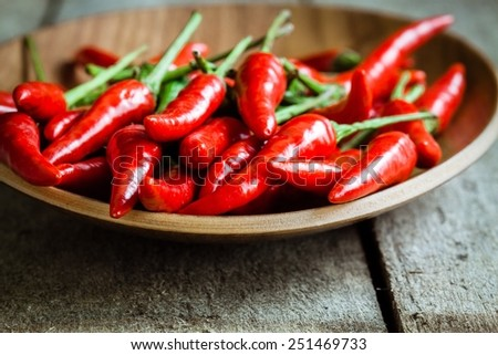 red hot chili peppers in the dish on wooden rustic background - stock photo