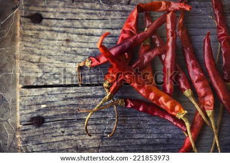 Red hot chili peppers on an old wooden table texture. Spicy pepper. Food photography with cope space. Shallow depth of field, selective focus - stock photo