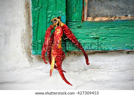 Red hot chili peppers on on the background wall of the old house - stock photo