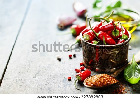 Red Hot Chili Peppers with herbs and spices over wooden background - cooking or spicy food concept - stock photo
