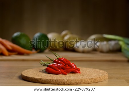 Red hot chilli peppers on a wooden table with vegetables on the background - stock photo