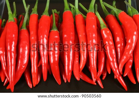 Red hot chilli peppers on the black background. - stock photo