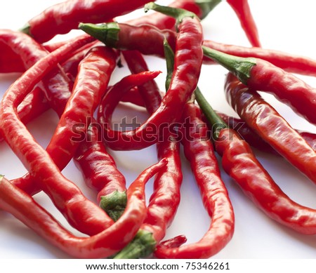 Red Hot Chillies a bunch of chillies resting on a white surface - stock photo