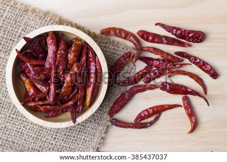 Red hot dry chili peppers in a wooden bowl on wooden background - stock photo