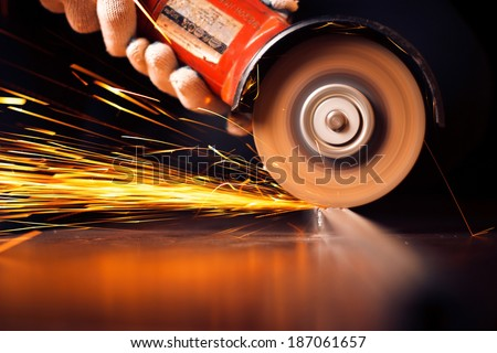 Red hot sparks at grinding steel material. Close up - stock photo