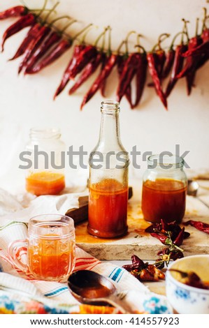 Red hot sweet chilli sauce over old white wooden background. Rustic styling. Pepper sauce  with  parsley and garlic in glass jar. Home made ketchup in a jar. Canning Marinara sauce - stock photo