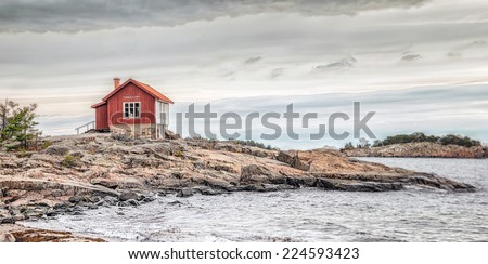 Red house at sea shore in the baltic sea in dull colors in autumn - stock photo