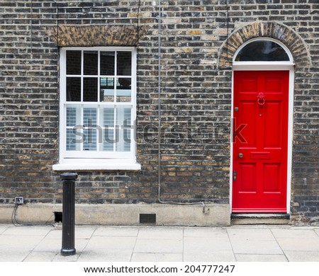 Red house door on a London street - stock photo
