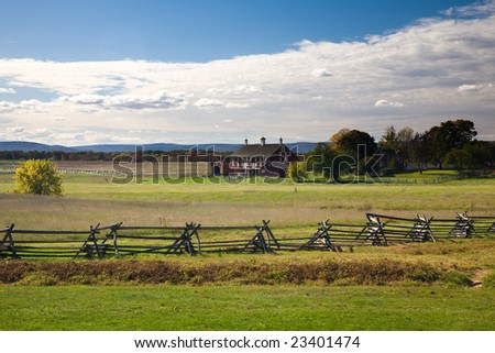 Red house in autumn field, forest in the distance, fence in the foreground - stock photo