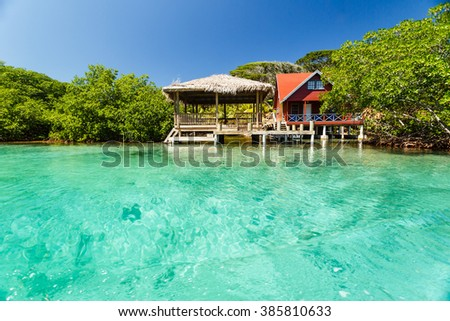 Red house on stilts with gazebo at secluded beach in Caribbean - stock photo
