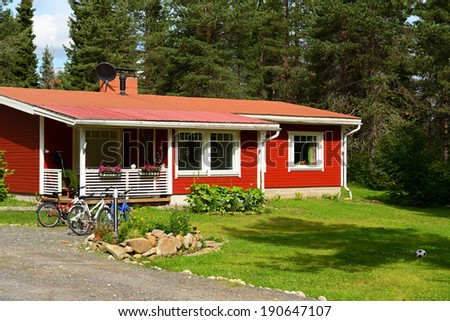 Red house with bicycles on a glade. Northern Finland, Lapland - stock photo