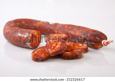 Red iberian chorizo with some cut pieces. Isolated over white background - stock photo