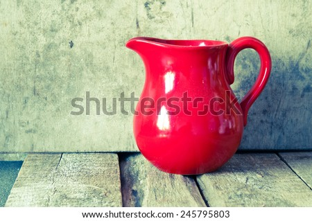 Red jug on a wooden table over vintage background - stock photo