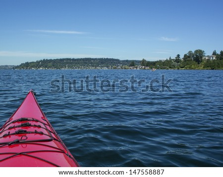 Red kayak with blue water and land in the background. - stock photo