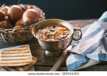 Red kidney bean soup with carrots and barley on wooden table - stock photo