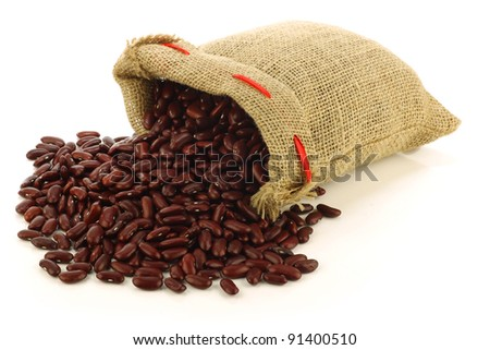 red kidney beans in a burlap bag and an aluminum scoop on a white background - stock photo
