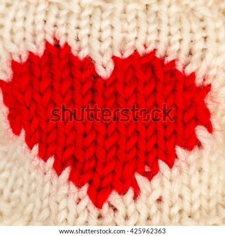 Red knitted wool heart on  white knitted background - stock photo