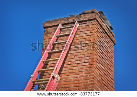 Red Ladder Against Old Chimney - stock photo