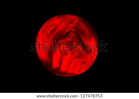 Red Laser Marble / A red translucent marble light painted with a laser light. - stock photo