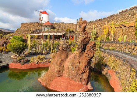 Red lava rock in pond and windmill in tropical cactus garden in Guatiza village, Lanzarote, Canary Islands, Spain  - stock photo
