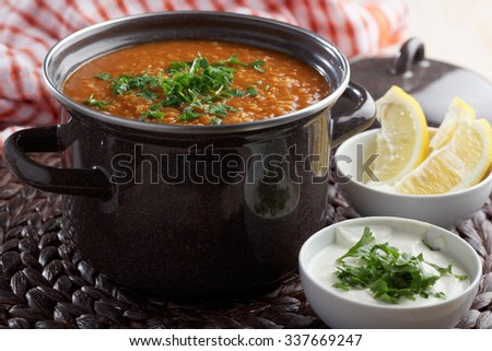 Red lentil soup and Greek yogurt with parsley on a rustic table - stock photo