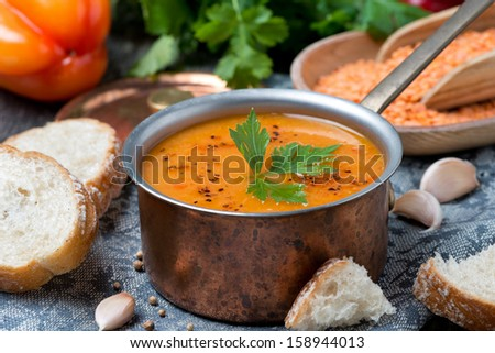 red lentil soup with pepper and spices in a copper saucepan, horizontal, close-up - stock photo