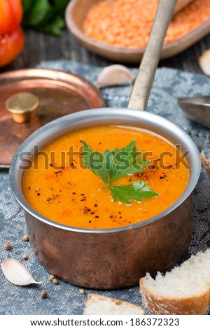 red lentil soup with spices in a copper saucepan, close-up - stock photo