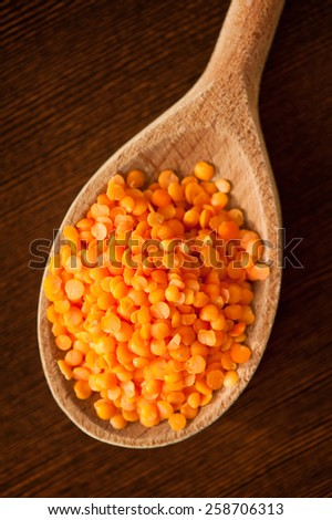 Red lentils wooden spoon, healthy red raw seeds heap lying on dark board in studio shot, vertical orientation, nobody. - stock photo