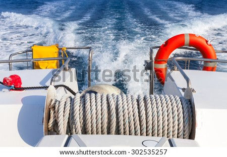 Red lifebuoy and winch with rope on stern of fast safety rescue boat - stock photo
