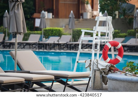 red lifebuoy for life safety on life guard chair at swimming pool - stock photo