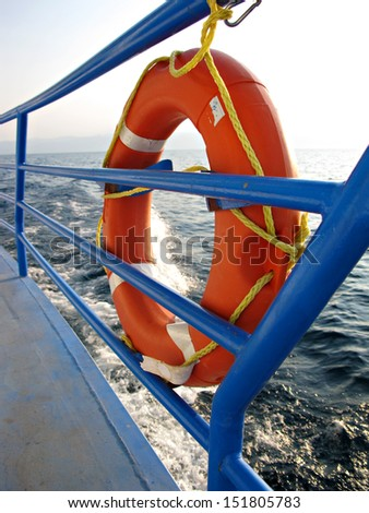 Red Lifebuoy in front of the blue sea  - stock photo