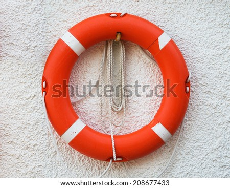 Red lifebuoy on the wall - stock photo