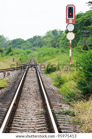Red light of signal pole shows for the train leaving the station - stock photo