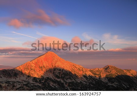Red light over the mountain peaks at dawn - stock photo