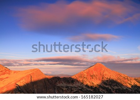 Red light shines on the mountain peaks at sunrise - stock photo