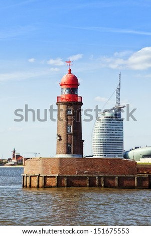 red lighthouse at the harbor entrance of Bremerhaven, contemporary buildings in background - stock photo