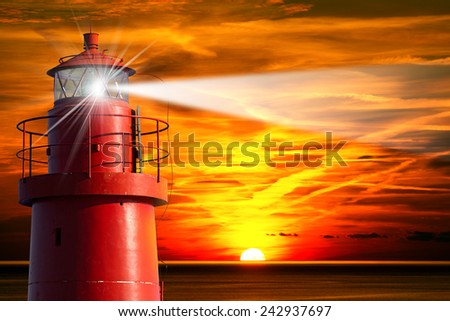 Red Lighthouse with Light Beam at Sunset. The top of a red and metallic lighthouse with light beam at sunset with clouds - stock photo