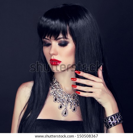 Red lips and manicured nails. Beautiful brunette woman wearing in luxury necklace, over back background - stock photo