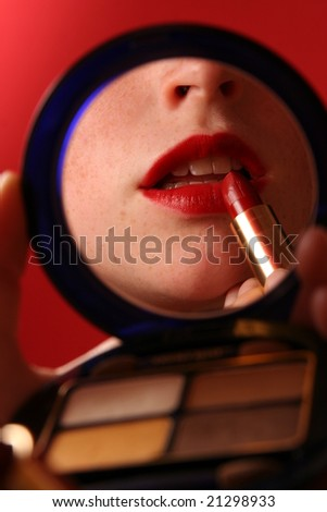 Red lips with lipstick in a makeup mirror - stock photo