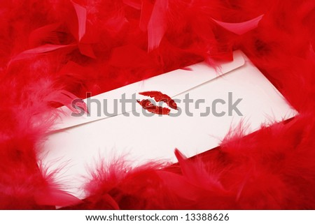 red lipstick kiss on letter envelope surrounded by glamorous red feather boa  ( sealed with a kiss ) - stock photo